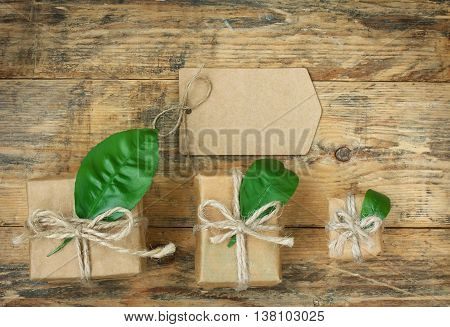 Three gift boxes with green leaves blank paper tag on an old wooden table top view