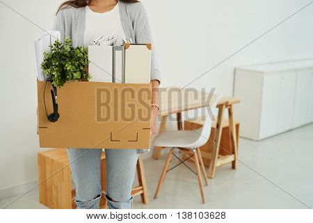 Cropped image of employee with cardboard box of her belongings