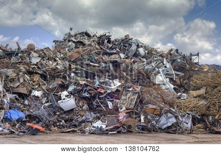Iron Raw Materials Recycling Pile over Cloudy Sky. Metal Waste Junkyard