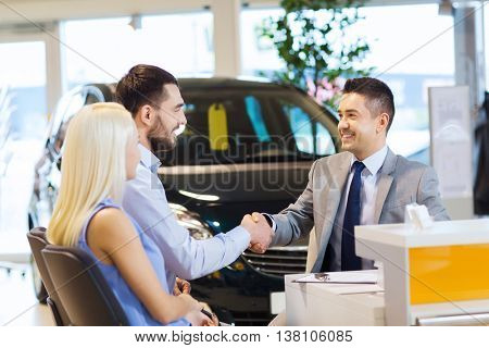 auto business, car sale, and people concept - happy couple with dealer shaking hands in auto show or salon