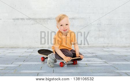 childhood, sport, leisure and people concept - happy little boy sitting on skateboard over city street background
