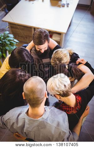 High angle view of creative business people forming huddle in office