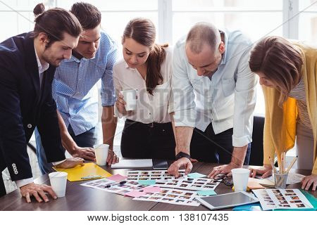 Photo editors looking at photos on table in creative office