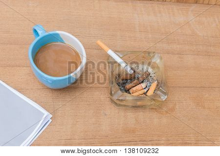Coffee and cigarette ashtray wooden table background, Top view