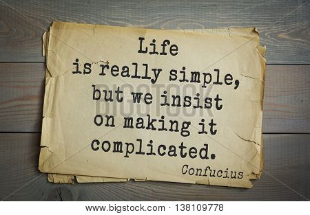 Ancient chinese philosopher Confucius quote on old paper background. Life is really simple, but we insist on making it complicated.