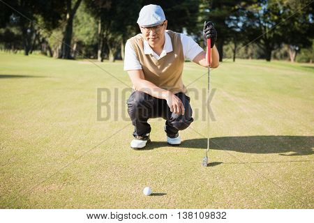 Golfer crouching and looking his ball on a field