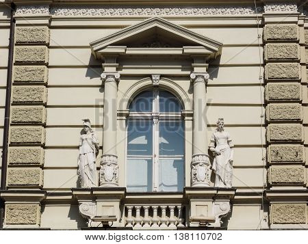 Neoclassical style window with allegorical sculptures of historical building