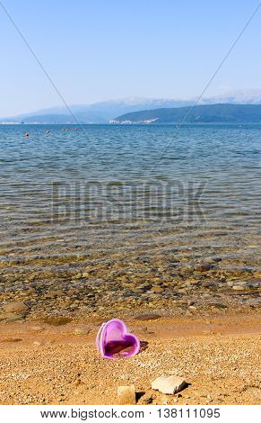 picture of a forgotten bucket on Beach on a Lake Prespa Macedonia