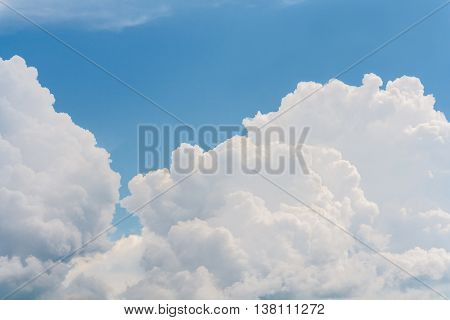 Landscape with white fluffy cumulus clouds in the blue sky