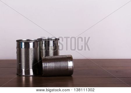 Battered tin cans on a rustic wooden background