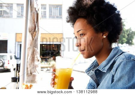 Fashionable Young African Woman Sipping Orange Juice