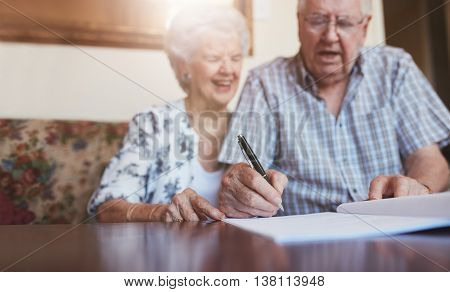 Senior Couple Signing Documents At Home