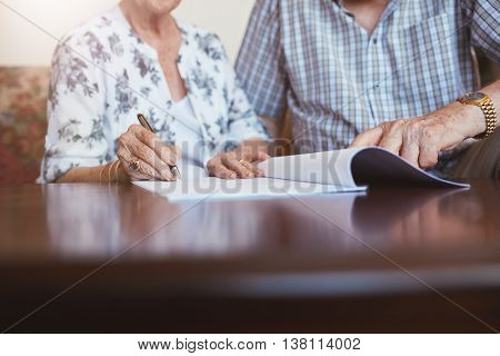 Senior Woman Signing Documents With Her Husband