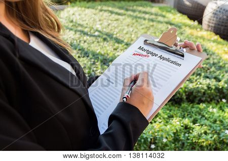 Businesswoman signing approved mortgage application in the garden.