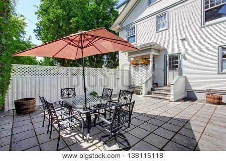 Concrete Floor Cozy Patio Area With Table Set And Patio Umbrella.