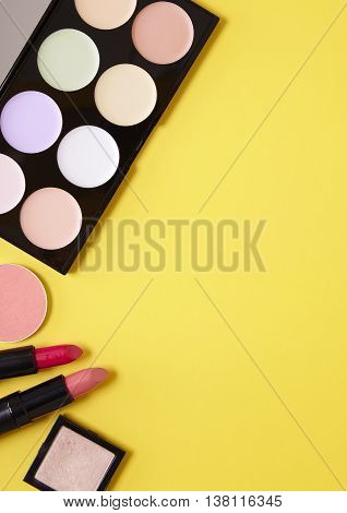 Make up and beauty products arranged to form a page border on a yellow background