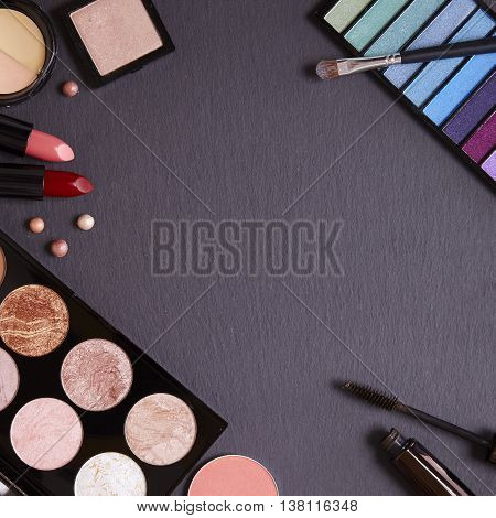 Assorted beauty products and make up brushes on a slate background forming a page border