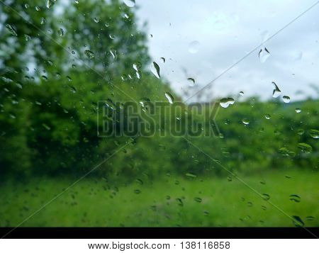 Rain Drops On A Window To A Green Garden