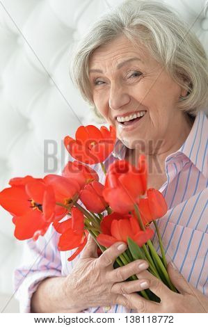 Portrait of a senior woman with blooming poppies