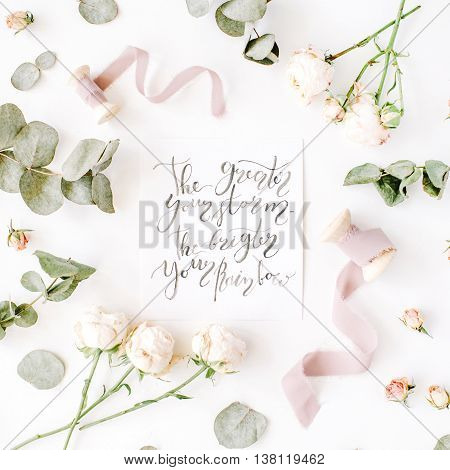 inspirational quote the greater your storm the brighter your rainbow written in calligraphy style on paper with pink roses and eucalyptus branches on white background. flat lay top view