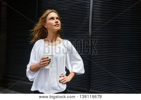 Portrait of dark background of young woman with waving blonde hair curiously looking up and holding coffee