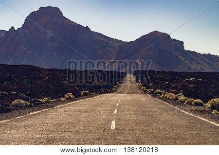 Straight empty desert road with mountains in haze on background Tenerife Canary islands Spain