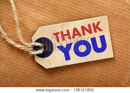 The words Thank You on a price or luggage tag with string and a brown wrapping paper background