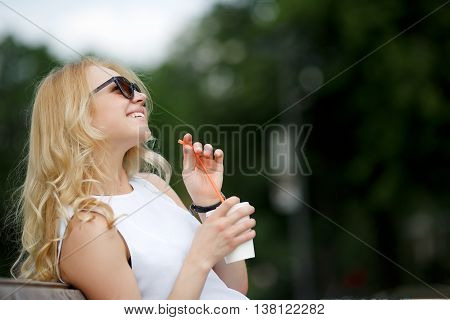 Young caucasian girl with curly blond hair looking up in sunglasses. Portrait in profile outdoors