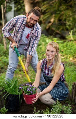 Portrait of happy young gardeners with potted plant and shovel at botanical garden