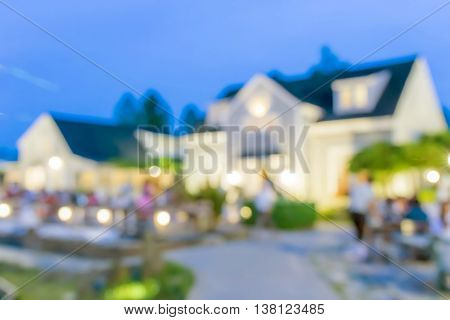 Blurred photo of outdoor restaurant with light bokeh in evening time for background usage.