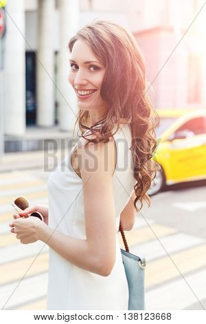 Beautiful young brunette woman in white dress on crosswalk background. Image with lens flare effect