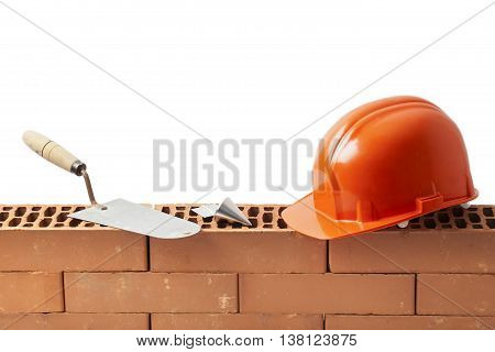 Construction tools trowel hard hat and plumb bob left on a new masonry isolated on white.