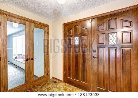 View To Brown Wooden Enterance Door. Tile Floor And Carpet Floor In The Next Room.