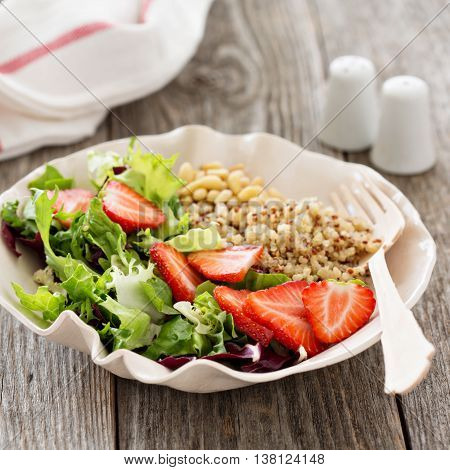 Quinoa salad with strawberries, pine nuts and greens