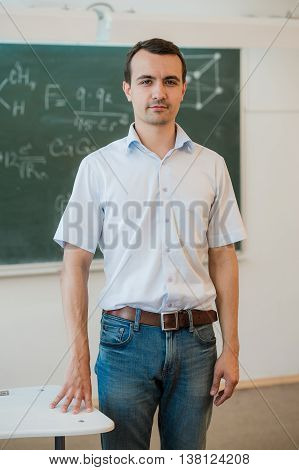 Handsome young male student or teacher standing relaxing against a green blackboard.