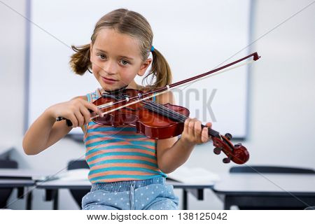 Portrait of smiling girl playing violin in classroom