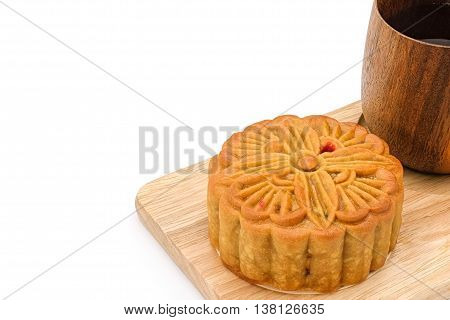 Mooncake and hot tea on wooden plate for the chinese Mid Autumn festival, on white background