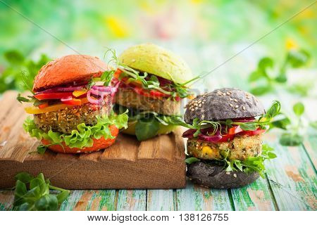 Red, green,black mini burgers with quinoa and vegetables