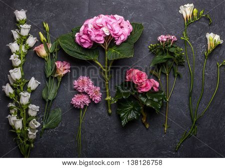 Various of pink and white flowers on the black background. Overhead view