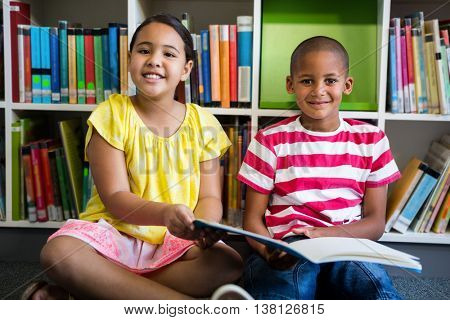 Porrait of elementary students reading book against bookshelf at library in school