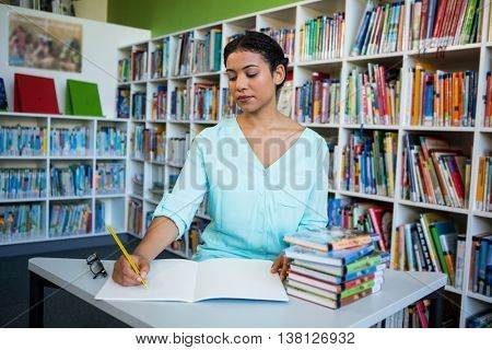 Young woman writing on notebook against bookshelf in library