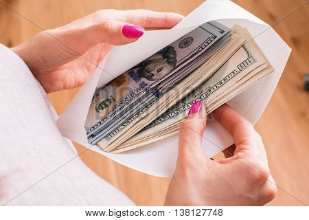 Closeup of female hands with envelope full of dollar banknotes on wooden background. Concept of corruption and bribery