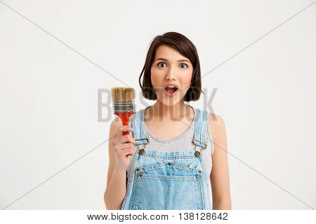 A portrait of young pretty girl, in gray shirt and denim overall, looking surprised, holding painting brush, isolated on white background