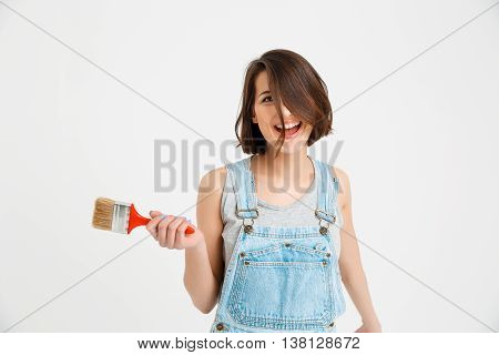 A portrait of young playful crazy beautiful girl, in gray shirt and denim overall, holding painting brush looking at camera, isolated on white background