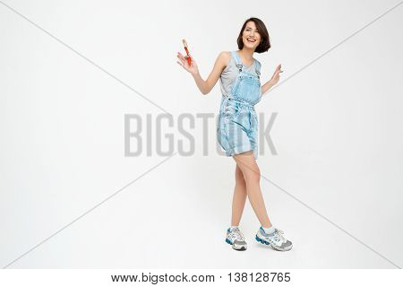 Full length portrait of a laughing pretty girl, in gray shirt and denim overall, holding painting brush, isolated on white background