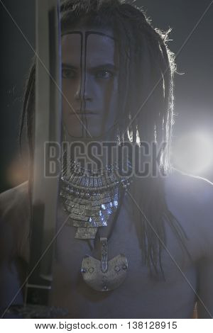 Young man's portrait. Stylish handsome sexy Guy with Dreadlocks and ethnic Jewelry Accessories (necklace bracelet) Close-up face. Tribal Style. Trendy youthful man's look with katana sword