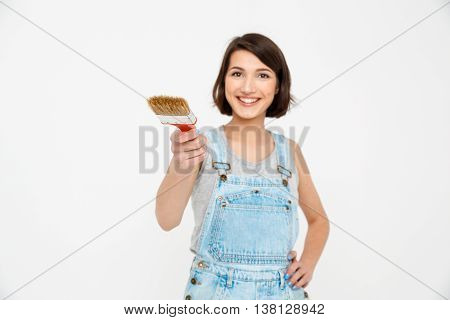 A portrait of young  beautiful girl, in gray shirt and denim overall, pointing forward with focus painting brush, looking at camera, isolated on white background
