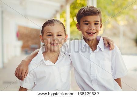 Portrait of smiling school kids standing with arm around in corridor at school