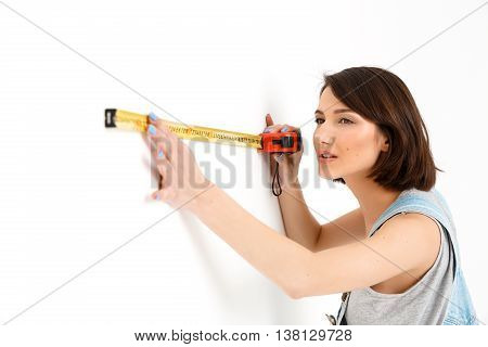 A portrait of young pretty girl, in gray shirt and denim overall, measuring the wall with tape, isolated on white background