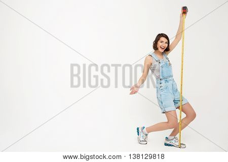 Full length portrait of a funny pretty girl, in gray shirt and denim overall, holding measure tape, isolated on white background